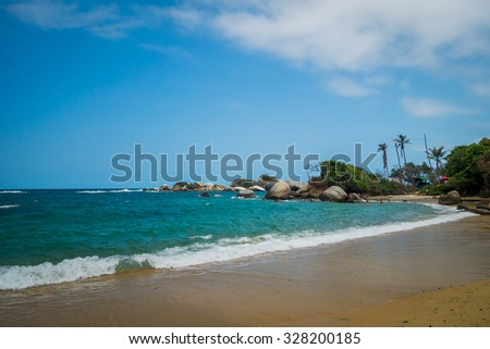 MAGDALENA, COLOMBIA - FEBRUARY 20, 2015: Unknown tourists enjoying the beautiful beach in Tayrona National Park, protected area in the caribbean region of Colombia