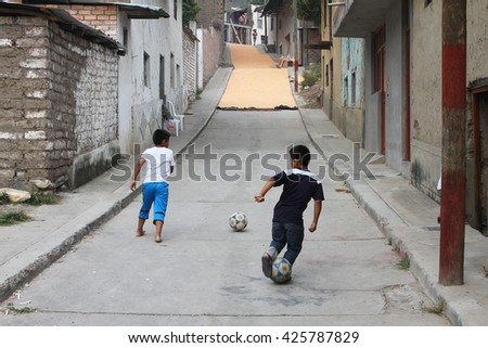 Magdalena, Peru - May 18, 2016: Two young boys practice soccer in front of street full of dry corn kernels in Magdalena, Cajamarca, Peru on May 18, 2016 - stock photo