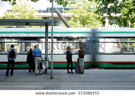 MAGDEBURG, GERMANY - JUNE 08: The station forecourt in Magdeburg with a passing tram and unknown people waiting at a bus stop on June 08, 2013 in Magdeburg, Germany.       - stock photo