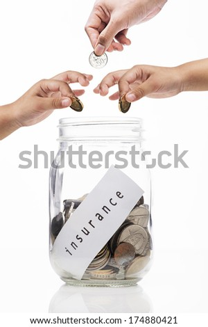 mage of  hands putting a coin into glass bottle,investment for insurance concept - stock photo