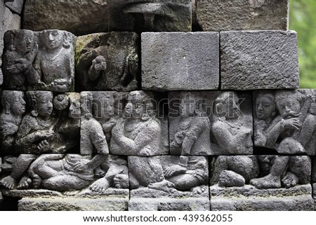 MAGELANG, INDONESIA - FEBRUARY 2, 2011: Ancient stone sculptures on the wall of Borobudur Temple. Borobudur Buddhist Temple is a UNESCO world heritage site. - stock photo