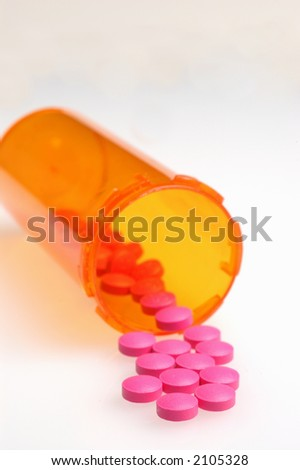 Magenta colored pills spilling from container onto white background