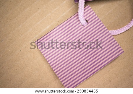 magenta colored stripes card stock with laces on a bright brown surface - stock photo