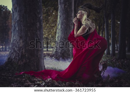magic, beautiful blond woman with red cape to the wind in a forest, romance and fantasy image