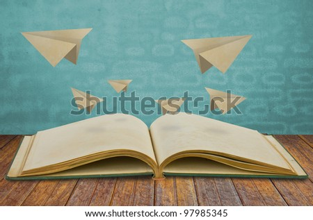 Magic book with paper plane - stock photo