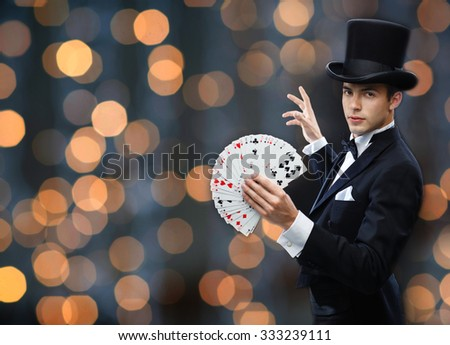 magic, gambling, casino, people and show concept - magician in top hat showing trick with playing cards over nigh lights background - stock photo