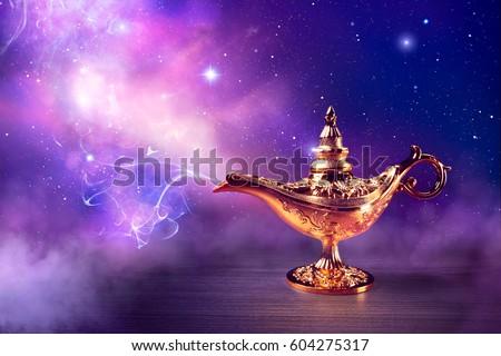 Magic genie lamp with smoke on a dark background
