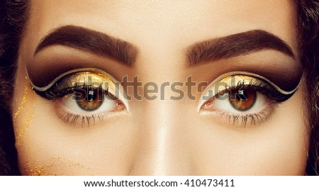 Magic Girl Portrait in Gold. Golden Makeup, close-up portrait in studio shot, color