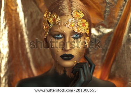 Magic golden girl with bright makeup. Streams of gold, shiny tears drops on the cheeks, black hand in the paint for body art. Big lips, long fingers, decorations, accessories. Professional photo, idea - stock photo
