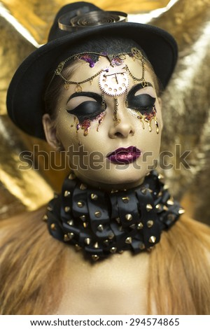 Magic golden girl with bright makeup. Streams of gold, shiny tears drops on the cheeks, black steam punk hat, big collar, body art. Pink lips, chins, decorations, accessories. Professional photo, idea - stock photo