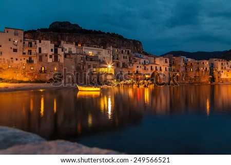 magic harbor view of old houses in Cefalu at night, Sicily - stock photo