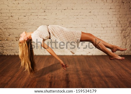 Magic moment - girl levitates on a medieval pictures background  - stock photo