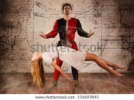 Magic moment - man in medieval suit performing magically levitating his girl assistant - stock photo