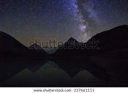 Magic night landscape with mountains, frozen lake and amazing starry sky. - stock photo