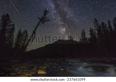 Magic night landscape with mountains, river and amazing starry sky. - stock photo
