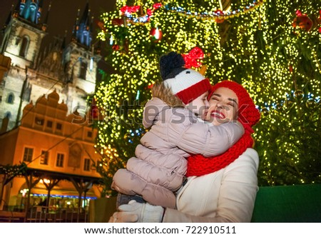 Magic on streets of the old town at Christmas. happy modern mother and daughter tourists at Christmas in Prague Czech Republic hugging