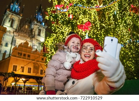 Magic on streets of the old town at Christmas. smiling young mother and daughter travellers at Christmas on Staromestske namesti in Prague Czech Republic with mobile phone taking selfie