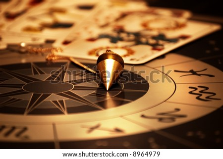 magic pendulum and cards of tarots on astrological background - stock photo
