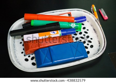 Magic pens, whiteboard markers and eraser on a plastic tray to be used in office meeting room or classroom