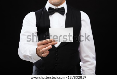 magic, performance, circus, casino and show concept - casino dealer holding white card - stock photo