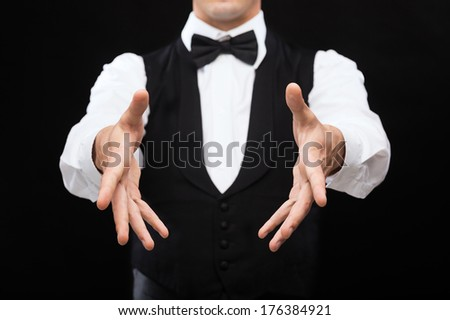 magic, performance, circus, casino and show concept - casino dealer showing trick - stock photo