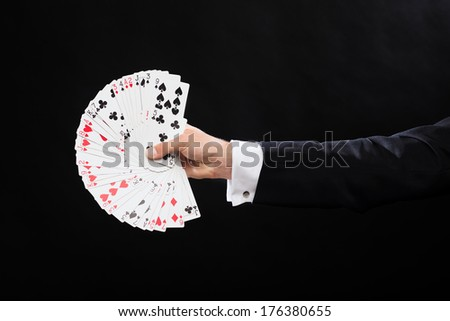 magic, performance, circus, gambling, casino, poker, show concept - close up of magician hand holding playing cards - stock photo