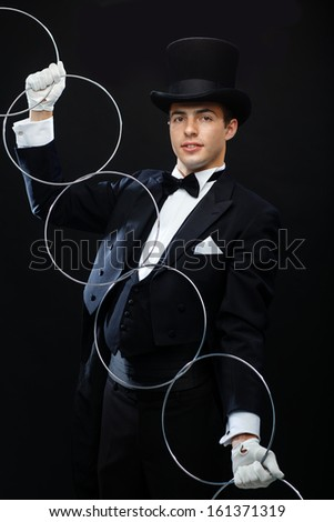 magic, performance, circus, show concept - magician in top hat showing trick with linking rings - stock photo