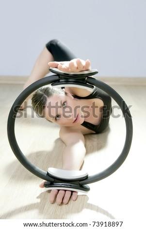 magic pilates ring woman aerobics sport gym exercises on wooden floor - stock photo
