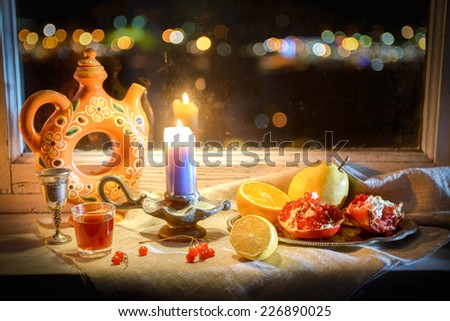 Magic Still Life With Candle Warm Light, Fruits, Jug, Wineglass And City Lights - stock photo