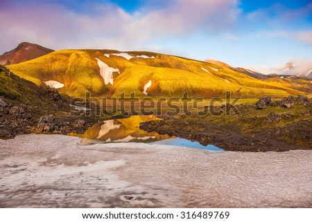 Magic sunrise in the Arctic. Light golden dawn illuminates the mountains and glaciers national park Landmannalaugar in Iceland - stock photo