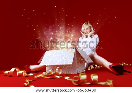 Magic surprise for a pretty blonde! Charming girl in white dress spread shot. Gift box in center. Light beams and stars coming from the box. Red background. Amazing face expression. Sense of holiday. - stock photo