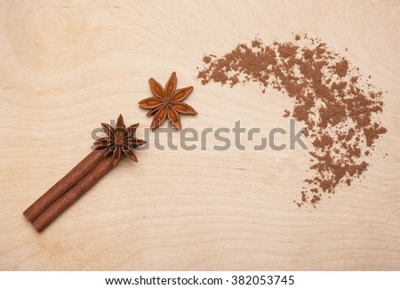 Magic wand made of cinnamon stick, star anise and cocoa powder on wooden background. Magic aromatic spices for healthy and flavored food. - stock photo