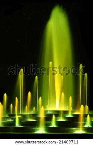 magic water fountain in yellow color - stock photo