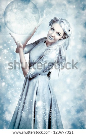 Magic Winter Girl Wearing Luxury Fashion And Elegant Hairstyle With Beautiful Make-up Holding Crystal Ball In Falling Snow - stock photo