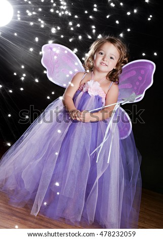 "Magical! Adorable toddler wearing a long tutu dress, butterfly wings and holding a magic wand. Background light and ""sparkles"" for effect."