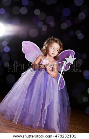 "Magical! Adorable toddler wearing a long tutu dress, butterfly wings and holding a magic wand. Background light, lens flare, and ""sparkles"" for effect."