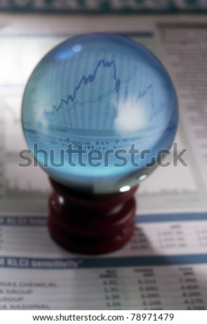 magical crystal ball on the finance section of newspaper - stock photo
