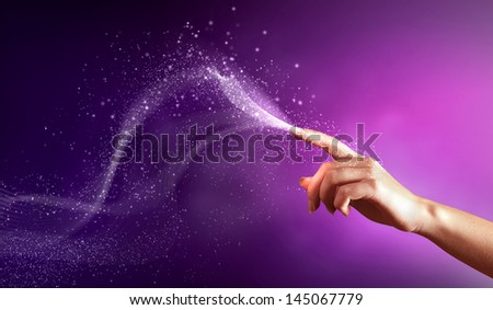 magical hand conceptual image with sparkles on colour background - stock photo