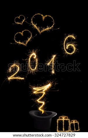 Magical new year. Magical fireworks from black top hat forming the digits 2016, gifts and heart shape isolated on black background. Happy new year background. - stock photo