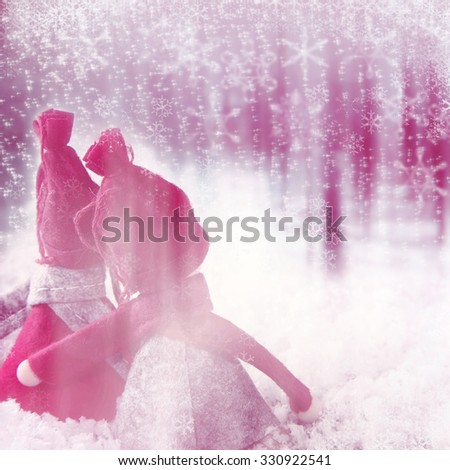 Magical pink handcrafted Christmas snowmen in an ethereal pink snowy winter landscape with copyspace for your seasonal greeting - stock photo