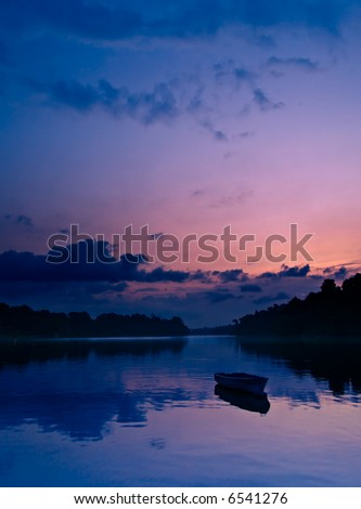 Magical Twilight silhouetting a moored boat with its reflection on calm waters of a lake