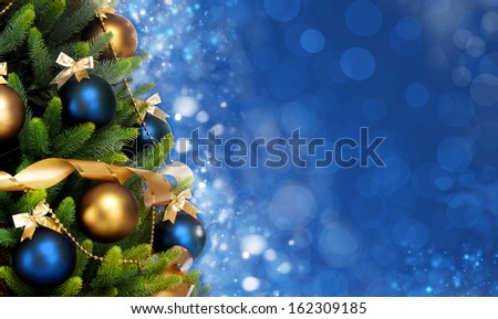 Magically decorated Christmas Tree with balls, ribbons and garlands on a blurred blue shiny, fairy and sparkling background, banner format - stock photo