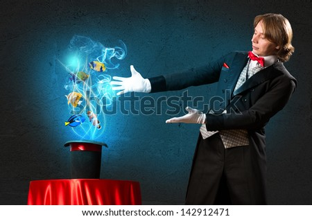 magician casts a spell over the cylinder, circling around the colorful fish