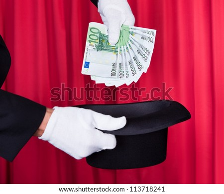 Magician Hand Holding 100 Euro Note From Hat - stock photo