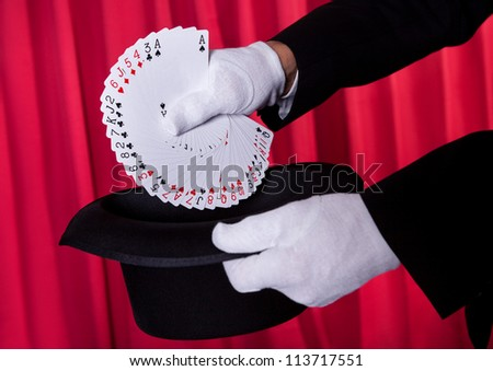 Magician Hand Holding Fanned Deck Of Cards From Hat - stock photo