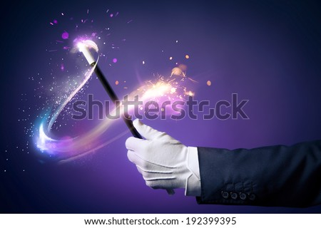 Magician hand with magic wand - stock photo