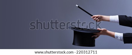 Magician hands with hat and magic wand - with copy space - stock photo