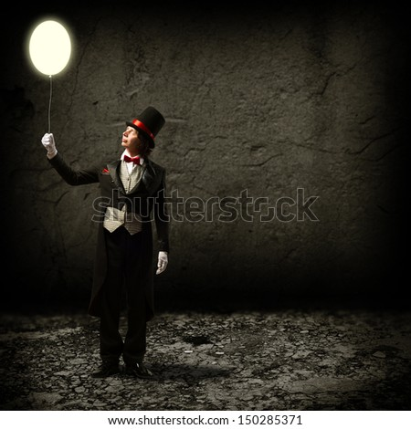 magician in top hat and tie, holding a glowing baloon, and staring at him - stock photo