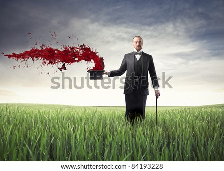 Magician on a green meadow with red paint coming out of his cylinder hat - stock photo