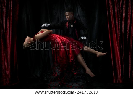 Magician performing levitation act on a stage - stock photo